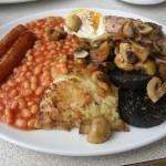 meniu englezesc - cârnați cu fasole, ciuperci, ochi, piure și șuncă prăjită
